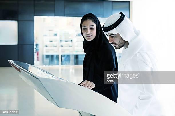 Arab familia utilizando la pantalla interactiva digital de terminal