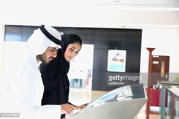 Arabische Familie mit interaktiven Bildschirm digitale Check-in-Schalter