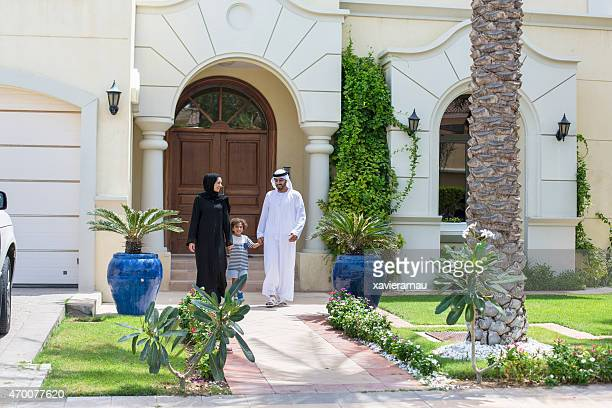 Arab family walking in front of their house