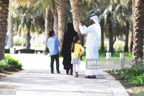 Arab father with his family taking a picture at a park using his smartphone