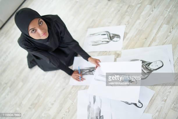 diseñadora de moda femenina árabe sentada en el piso - equidad de genero fotografías e imágenes de stock