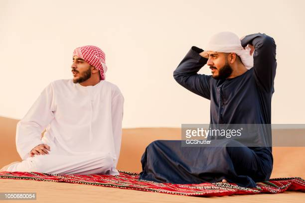 arab friends enjoying a relaxed weekend at the sand dunes - kaffiyeh stock pictures, royalty-free photos & images