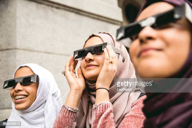 Arab friends looking at solar eclipse