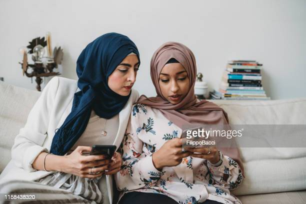 arab friends using mobile phones sitting on the sofa at home - dependency stock pictures, royalty-free photos & images