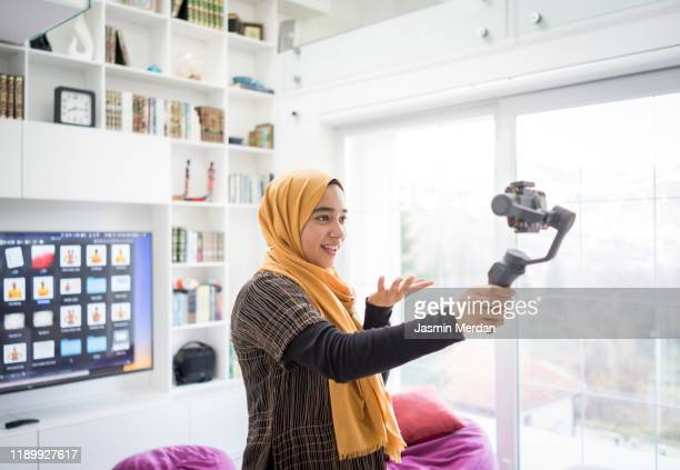 arab girl demonstrating hijab fashion online using steady cam with smartphone - live streaming stock pictures, royalty-free photos & images