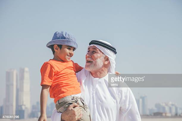 arab grandfather and little boy having fun at beach - arab old man stock pictures, royalty-free photos & images