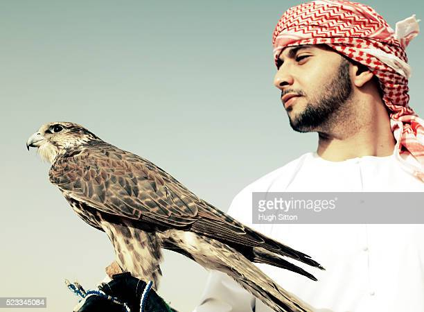 arab in the desert of dubai with falcon - hugh sitton 個照片及圖片檔