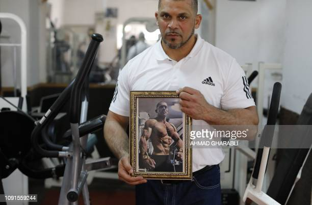 Arab Israeli bodybuilder and Muezzin Ibrahim Masri holds a picture of himself taken during a competition at a gym in the northern Israeli port city...