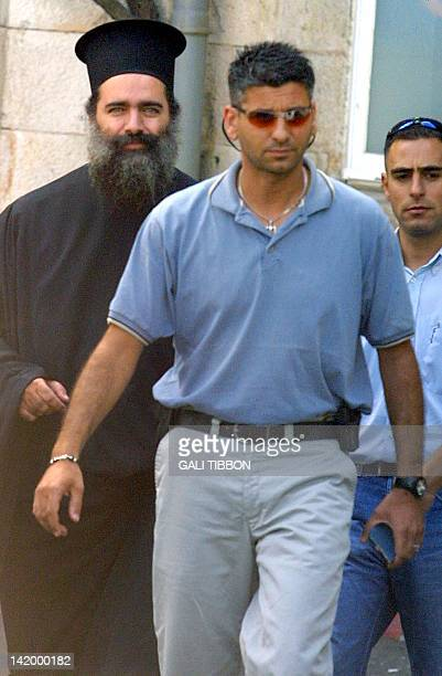 Arab Israeli Greek Orthodox archimandrite Theodosios Hanna walks out of the Jerusalem police station 22 August 2002 escorted by plainclothes...