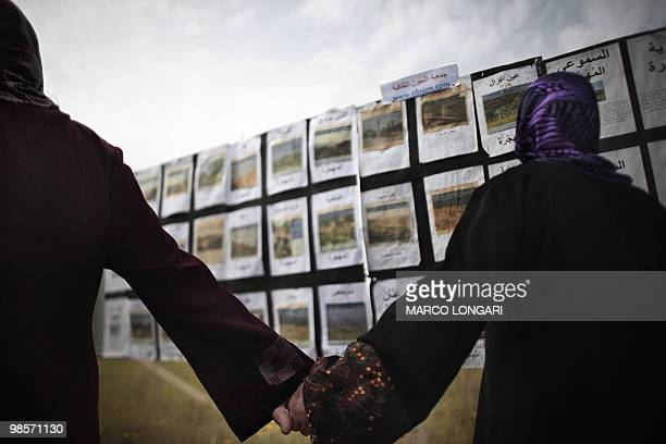 Arab Israeli women hold hands as they stand in front of pictures of disappeared Arab villages in Israel in the northern Israeli town of Tira on April...