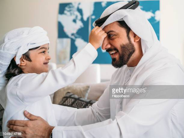 arab kid fixing keffiyeh to his father - headdress stock pictures, royalty-free photos & images