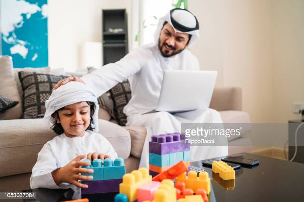 Arab kid playing with toys while his dad is working at home