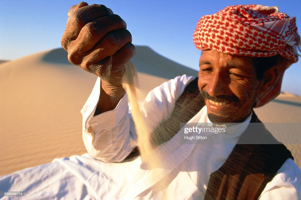 Arab lying satisfied in the desert : Stock Photo