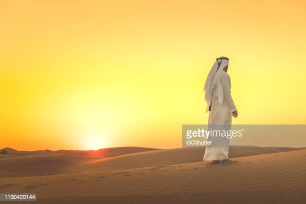 arab man admiring expansive dunes during sunset - ceremonial robe stock pictures, royalty-free photos & images