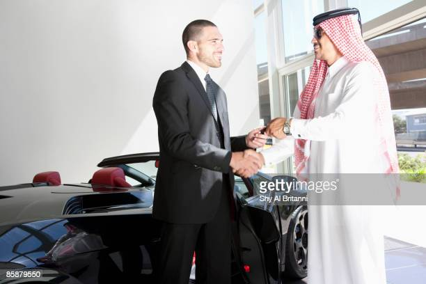 arab man and car dealer shaking hands besides car. - commercial event stock photos and pictures