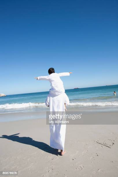 arab man carrying boy on shoulders at beach. - carrying stock pictures, royalty-free photos & images