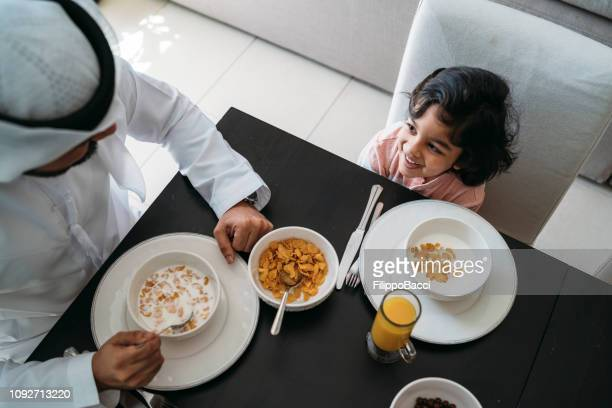 Arab man doing breakfast with his son at home