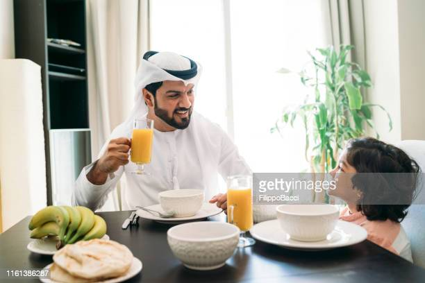 arab man doing breakfast with his son at home - kaffiyeh stock pictures, royalty-free photos & images