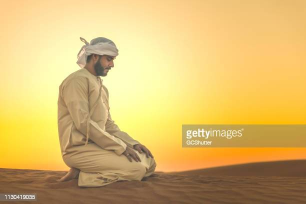 arab man doing evening prayers on the sand dunes - muslim prayer stock pictures, royalty-free photos & images