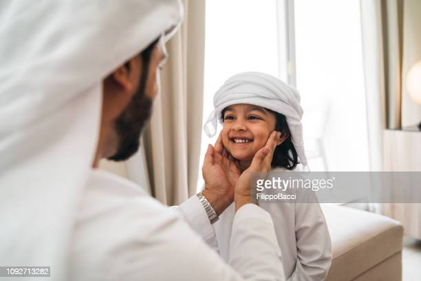 arab man fixing keffiyeh to his son - united arab emirates stock pictures, royalty-free photos & images