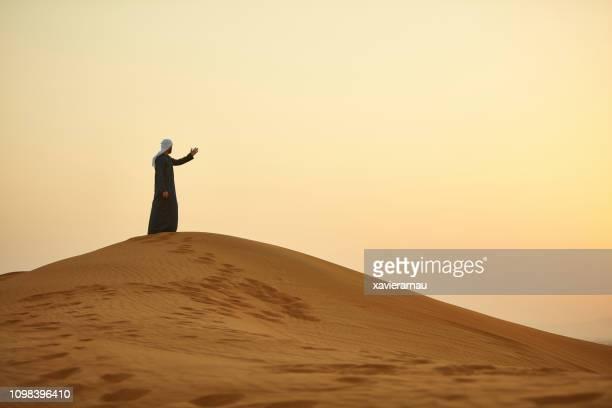 Arabische Mann gegen klaren Himmel gestikulieren