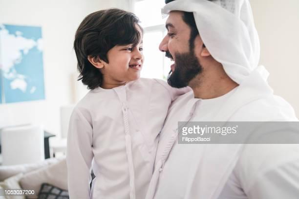 Arab man holding his son at home