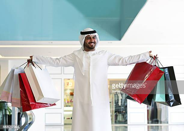 arab man in shopping center with bags - bahrain national day stock photos and pictures
