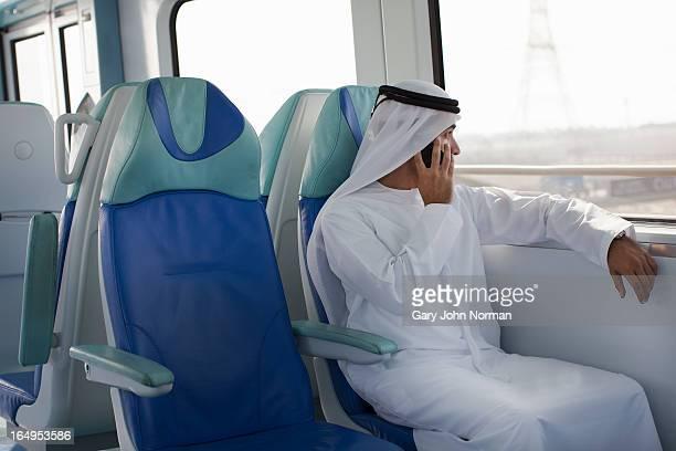 Arab man in traditional dress using metro in Dubai