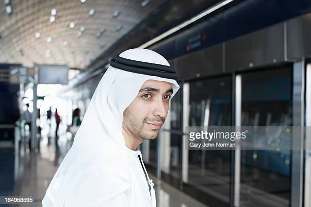 Arab man in traditional dress using metro in Dubai