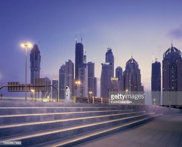 arab man in traditional robe waiting in front of dubai skyline at sunset - tradition stock pictures, royalty-free photos & images