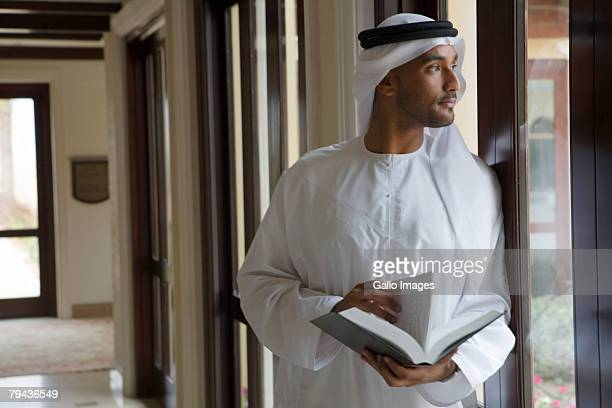 Arab man looking out window, holding book