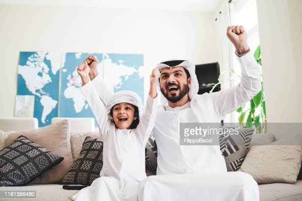 arab man looking tv at home during a sport event with his son - arabia stock pictures, royalty-free photos & images