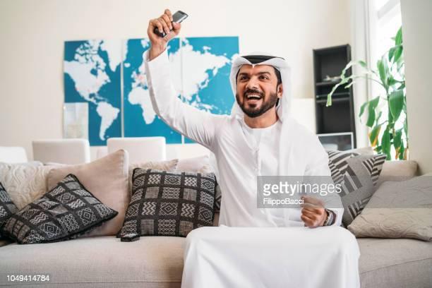 arabische man die tv thuis - menselijke ledematen stockfoto's en -beelden