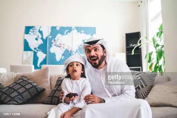 Arabische Mann sucht TV zu Hause mit seinem Sohn