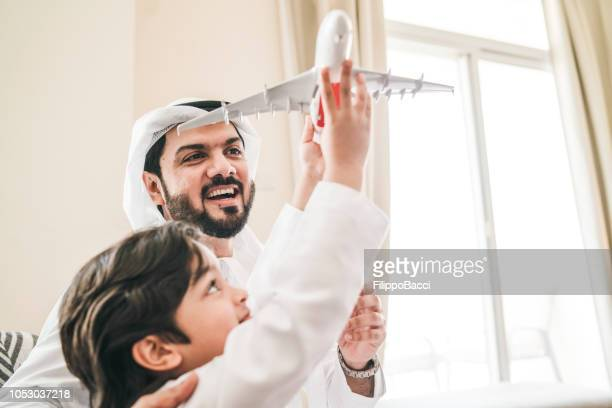 Arab man playing with his son at home