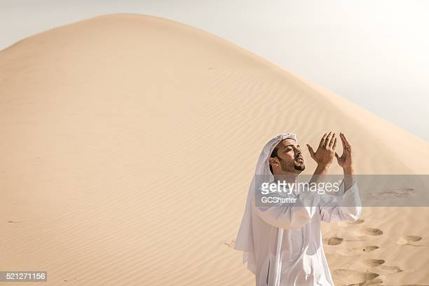 Uomo nel deserto arabo pregare