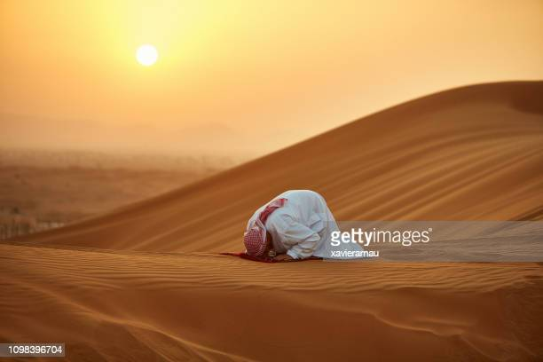 arab man praying on carpet in desert during sunset - praying stock pictures, royalty-free photos & images