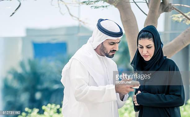 Arab Man showing Smartphone to an Arab Woman