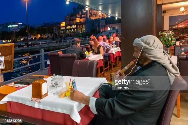 ストリートカフェ、イスタンブールでフックを吸っているアラブ人男性 - 水キセル ストックフォトと画像