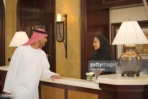 Arab Man Standing in a Lobby, Speaking to a Woman. Dubai, United Arab Emirates