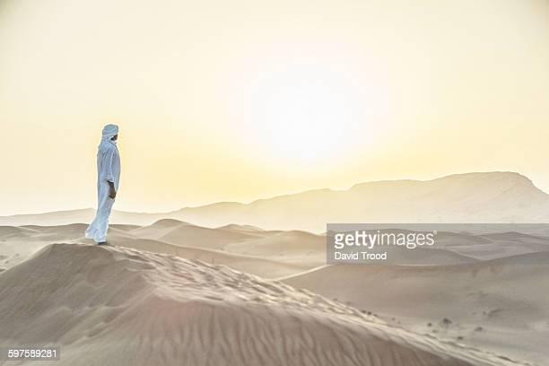 arab man standing in sand dunes near dubai. - one mature man only stock pictures, royalty-free photos & images
