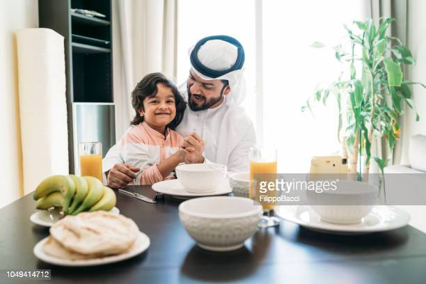 Arab man taking a selfie during breakfast with his son
