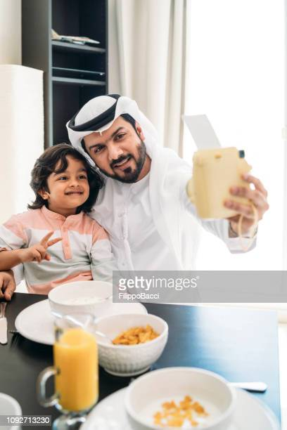 arab man taking a selfie during breakfast with his son - kaffiyeh stock pictures, royalty-free photos & images