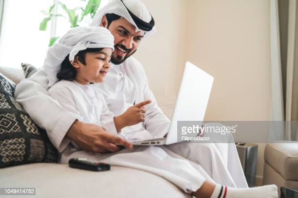 arab man using a laptop with his son on the sofa at home - arab family stock pictures, royalty-free photos & images