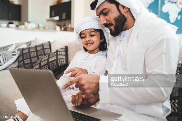 arab man using a laptop with his son on the sofa at home - geographical locations stock pictures, royalty-free photos & images