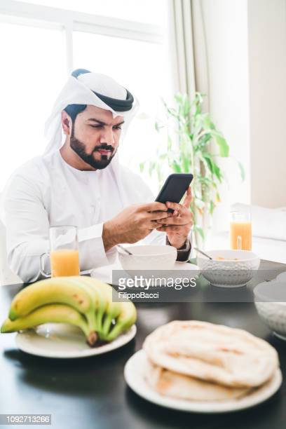 Arab man using a smartphone while doing breakfast at home