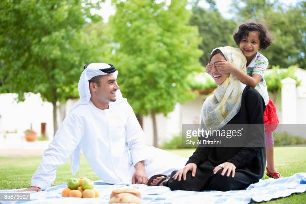 Arab man watching daughter covering mother's eyes.