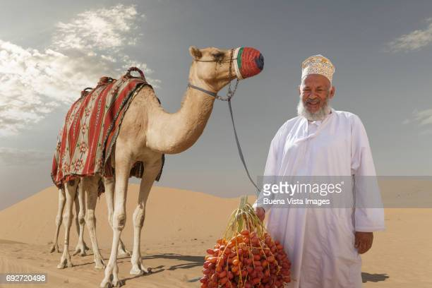 arab man with his camel and a bunch of dates - muscat governorate stock pictures, royalty-free photos & images