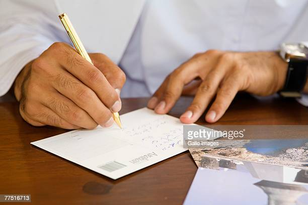 Arab man writing postcard on patio table. United Arab Emirates
