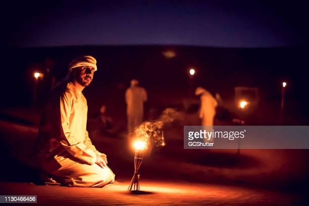 arab mean seated on the sand dunes near an oil lamp at a camp site - kaffiyeh stock pictures, royalty-free photos & images
